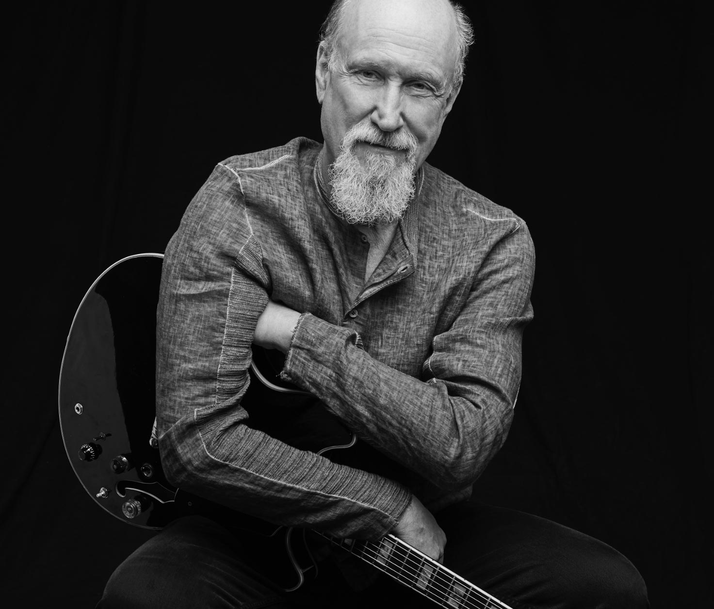 Smiling john Scofield with his guitar in arms