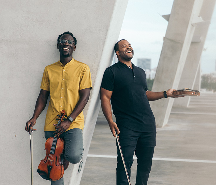 Black Violin, both members laughing and holding their violins